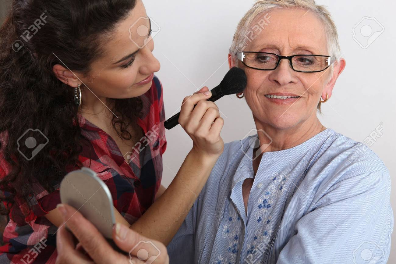 Young woman applying blush on her grandmother Stock Photo - 12019635
