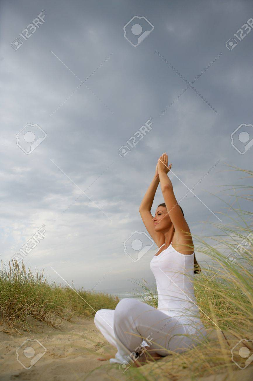 Woman practicing yoga in a field Stock Photo - 12019286
