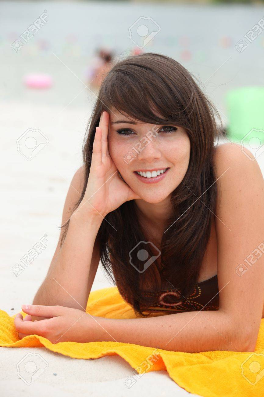 Young woman lying on a beach towel Stock Photo - 12019423
