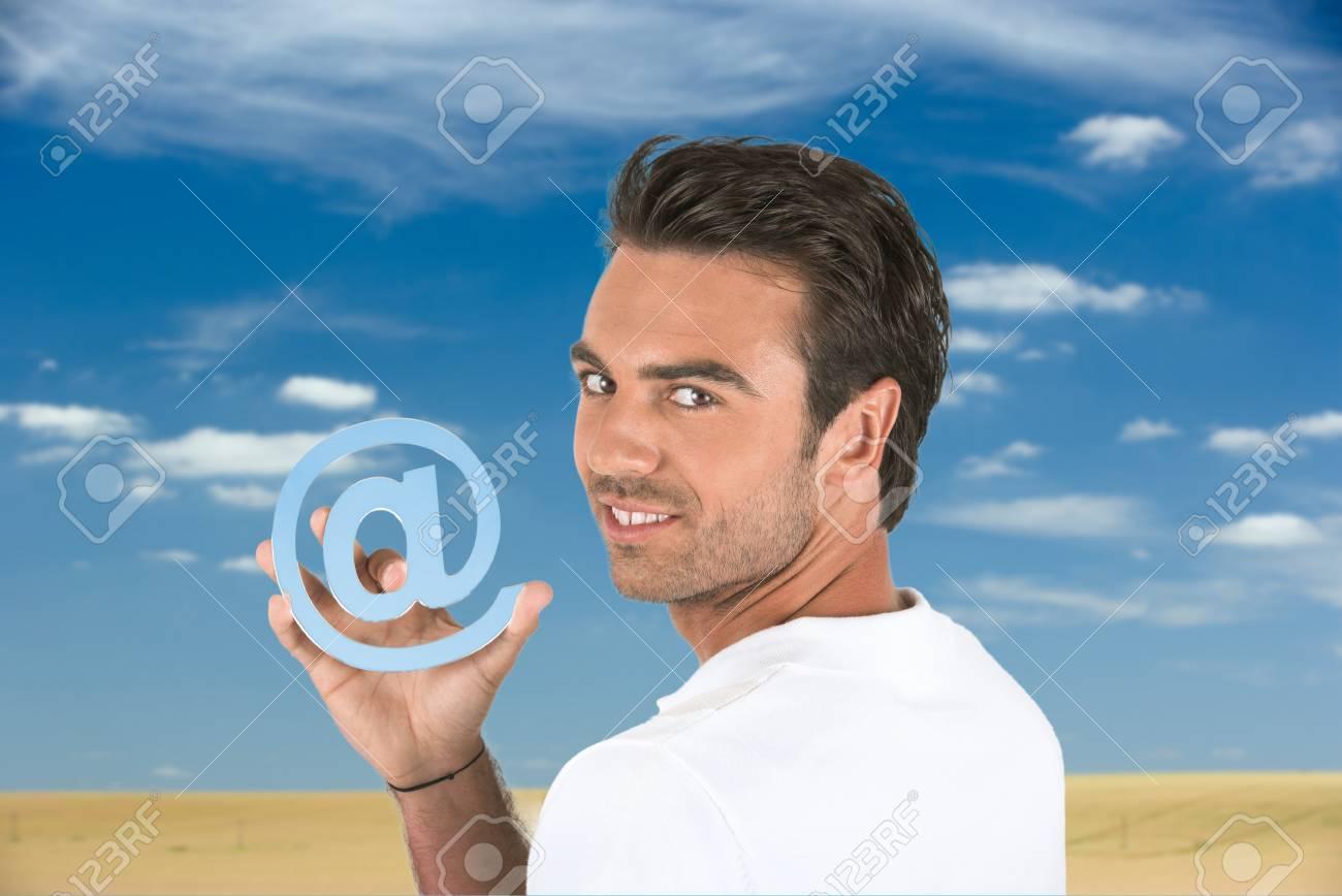 Man holding the at symbol Stock Photo - 12088428