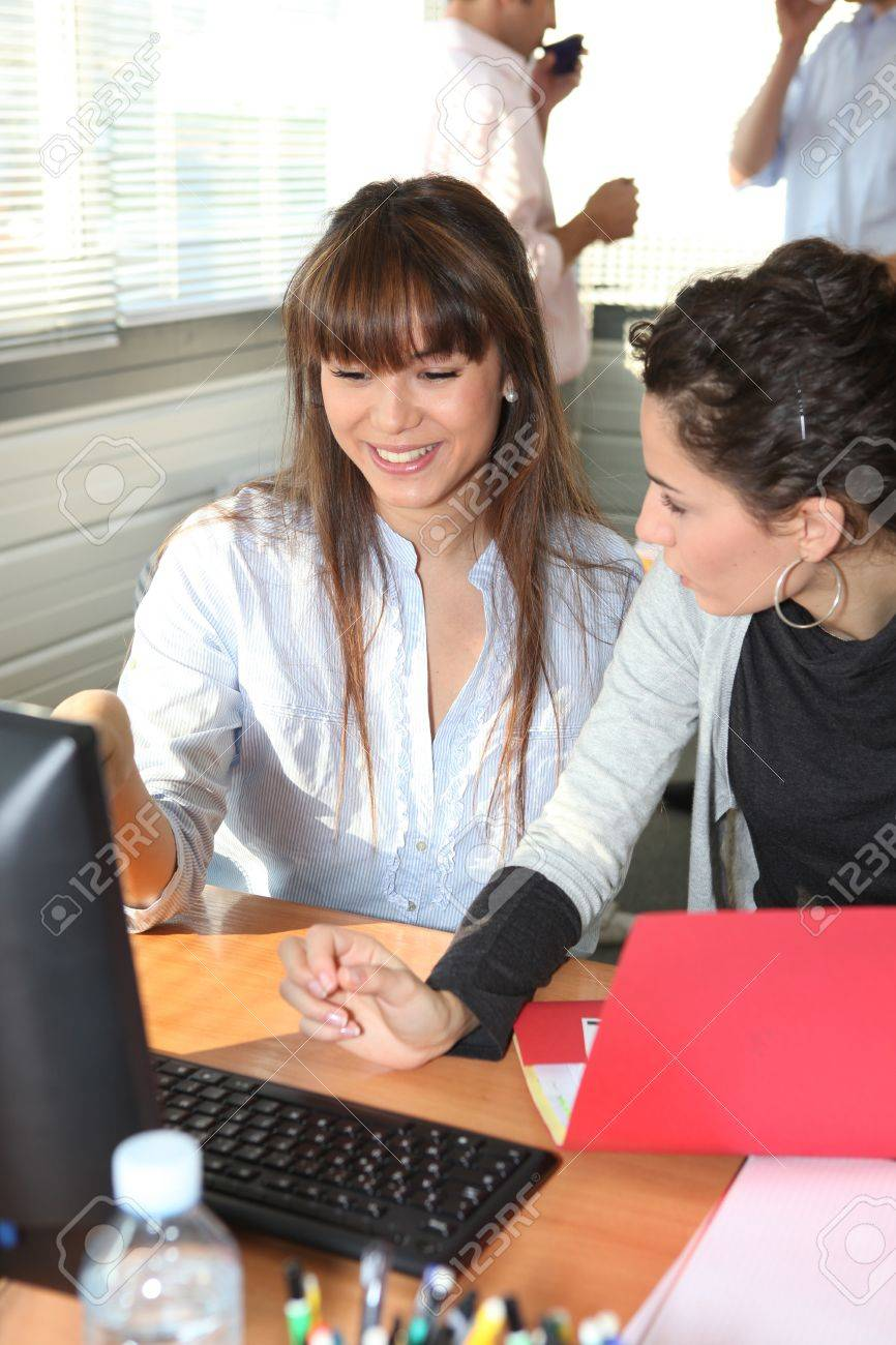 Woman smiling and chatting at an office desk Stock Photo - 12219717