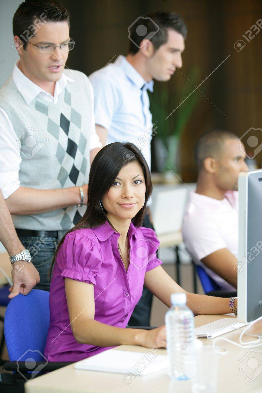 Woman working at a computer in a busy office Stock Photo - 12246422