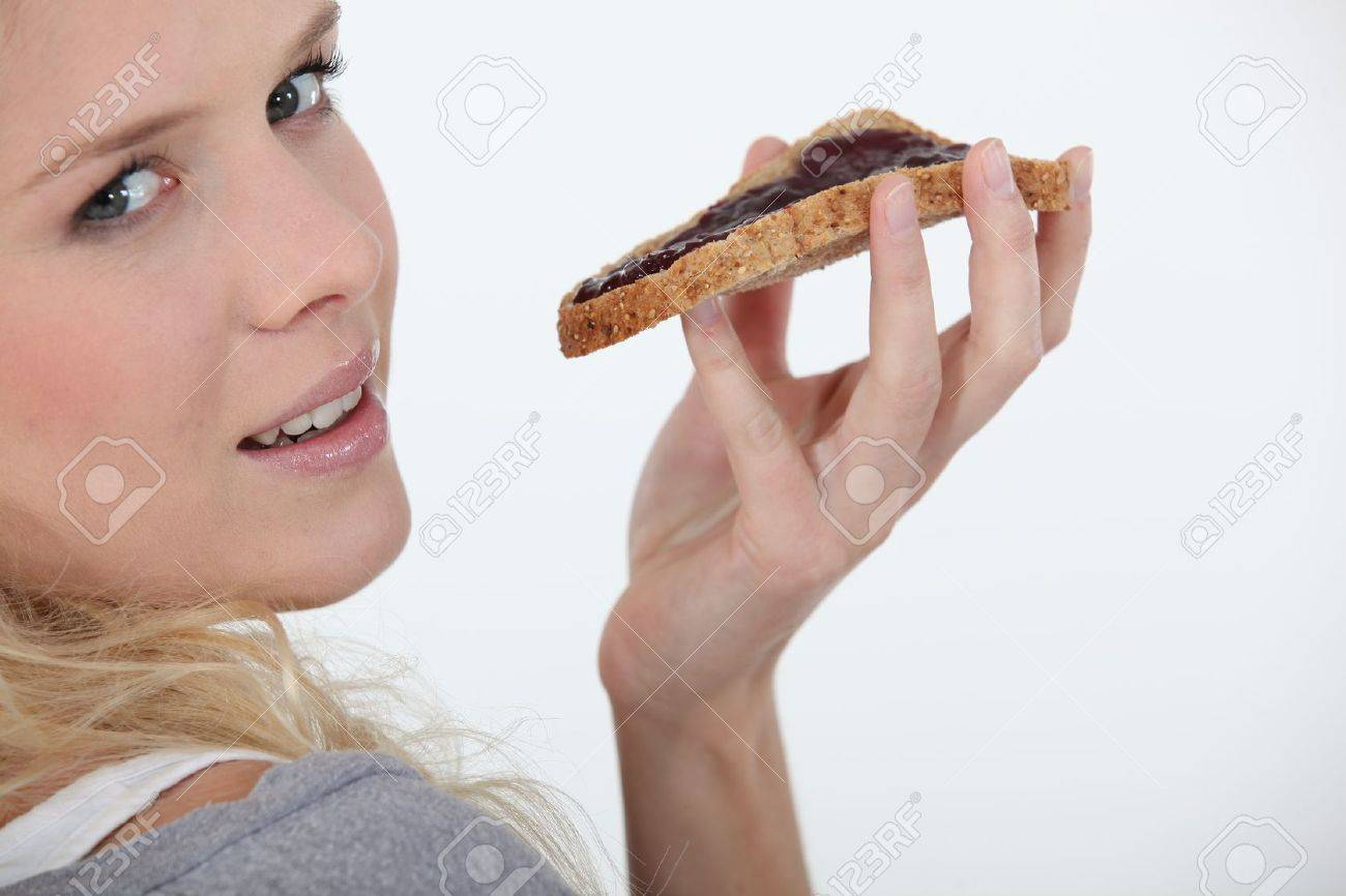 Blond woman eating chocolate spread on bread Stock Photo - 12244669