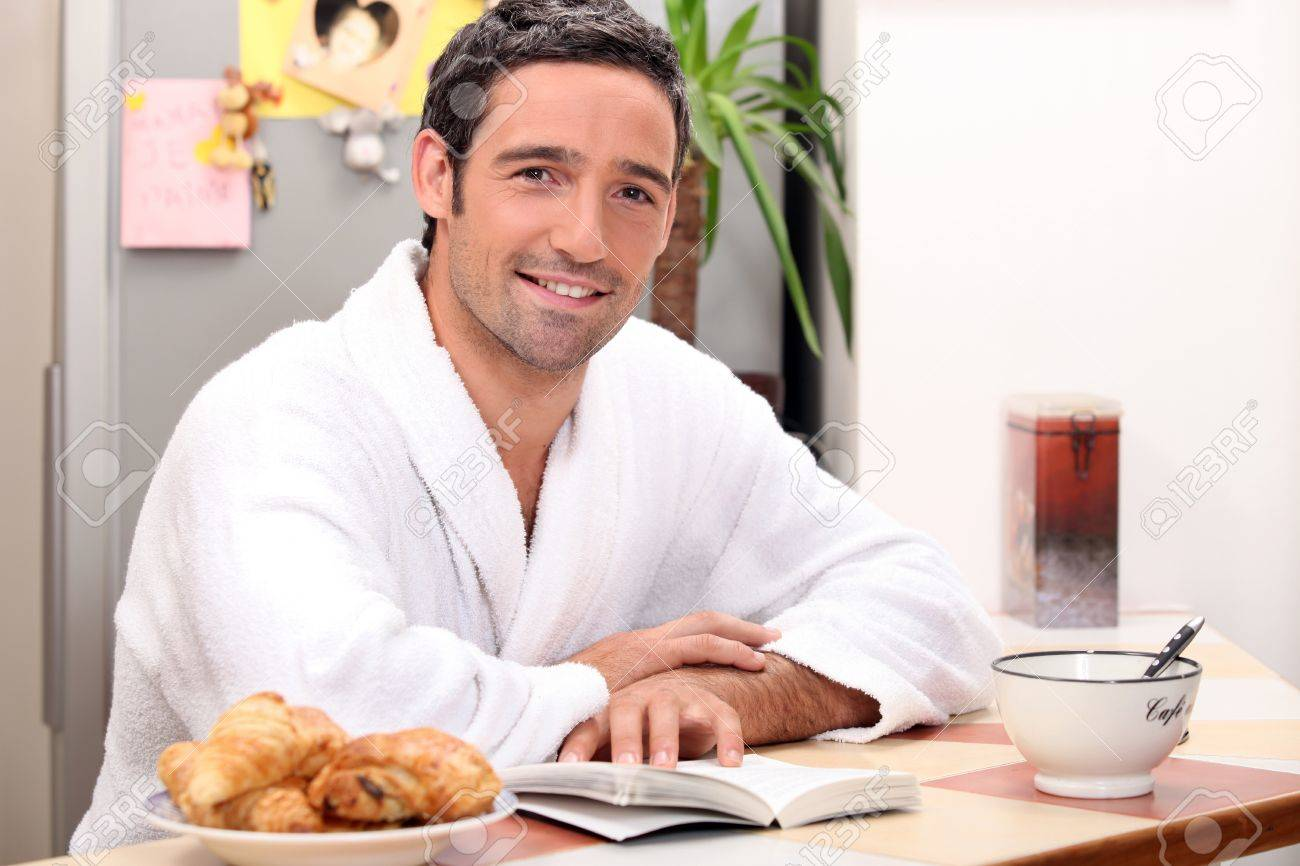 Man reading a book and eating a continental breakfast Stock Photo - 12248333