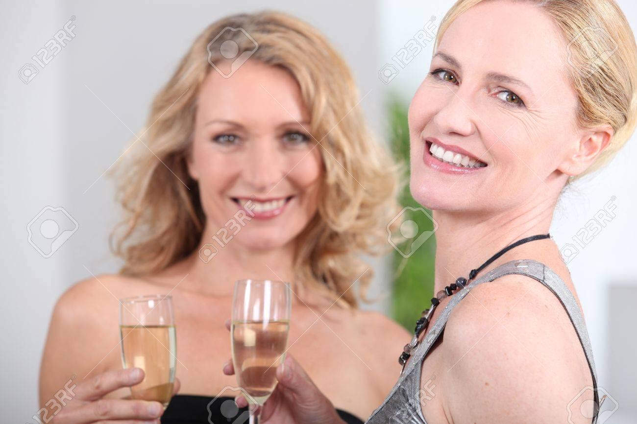 Two women with champagne flutes Stock Photo - 12251380