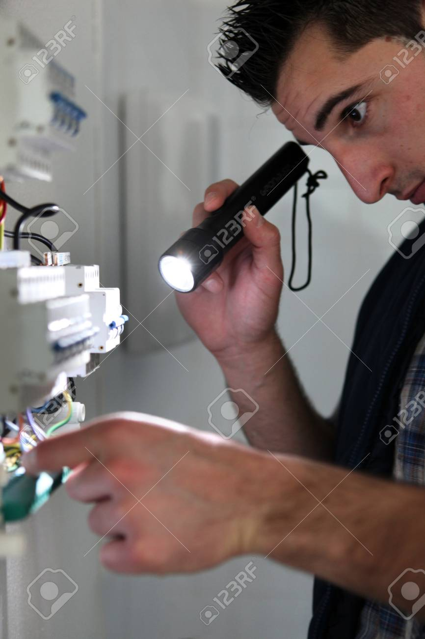 Electrician shining a torch on a fusebox Stock Photo - 12302721