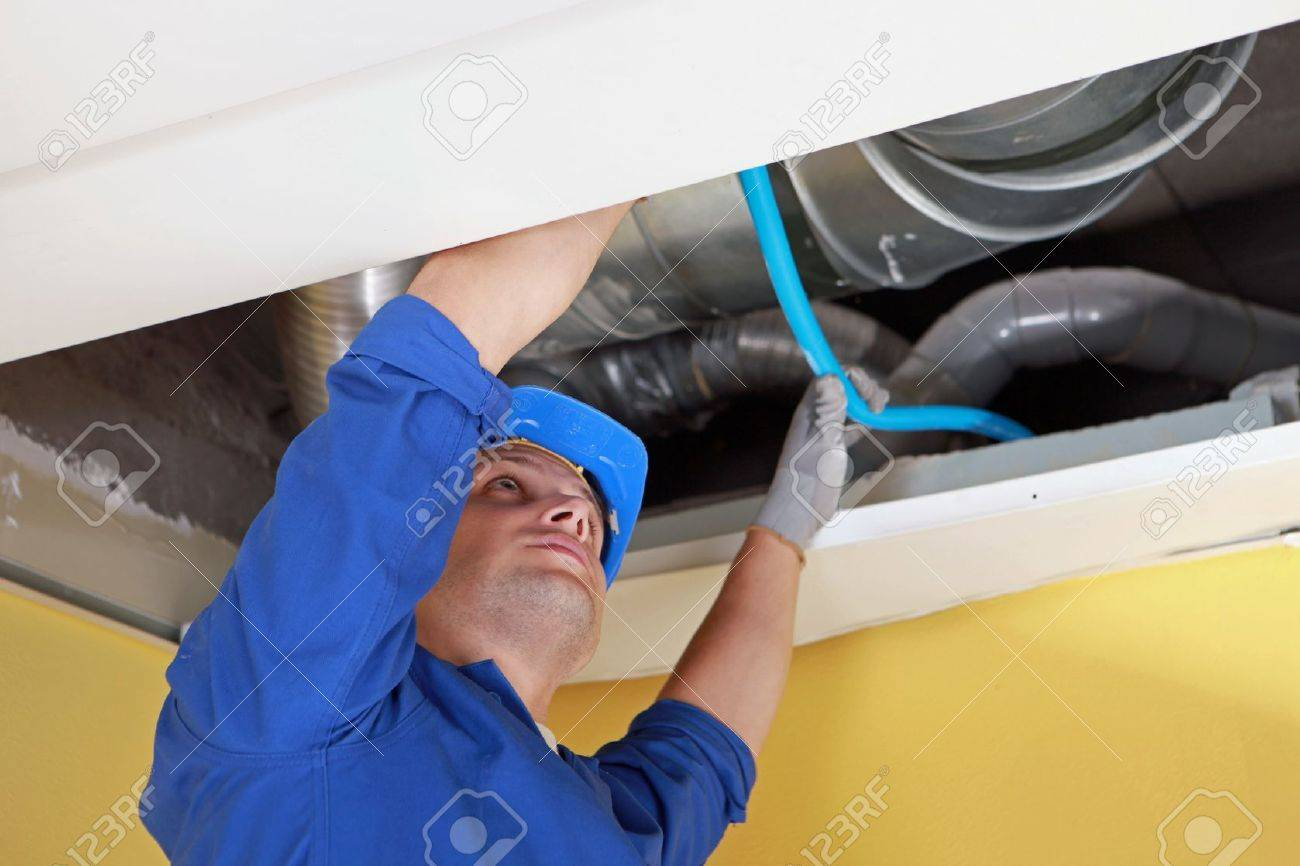 Worker holding blue pipe in place under air ducts Stock Photo - 12302635