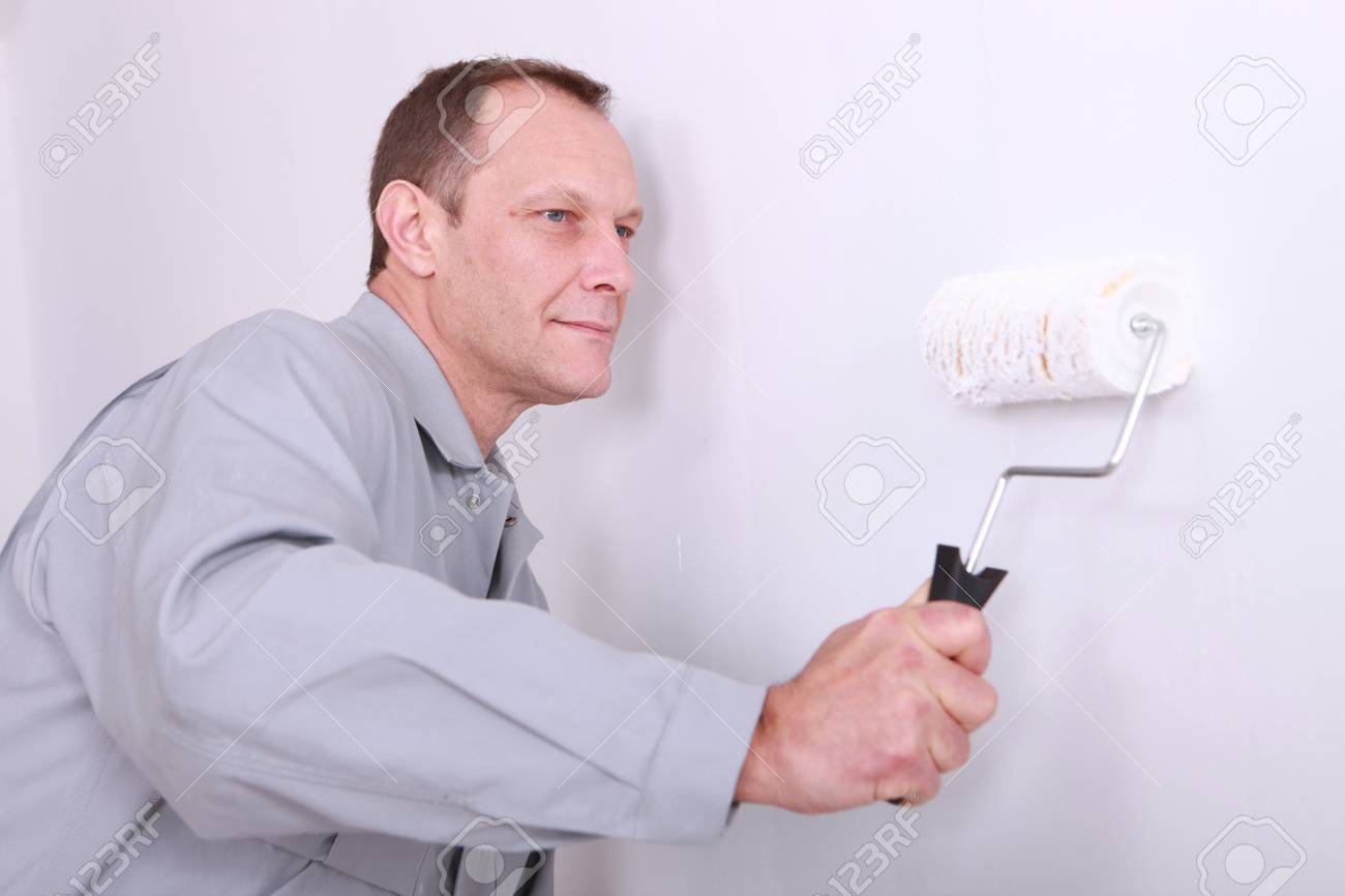 Decorator painting a wall white Stock Photo - 12302730