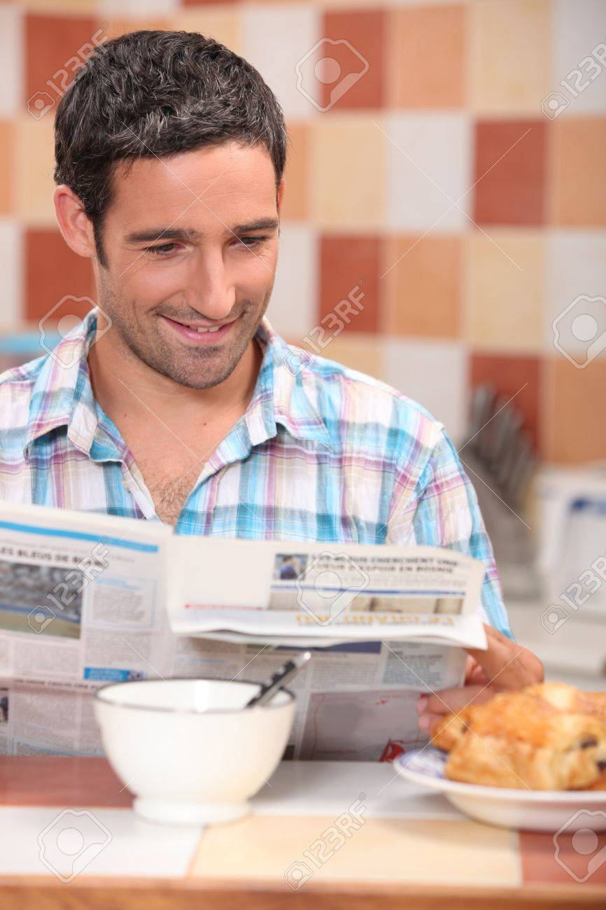 Man reading a journal over breakfast Stock Photo - 12302579