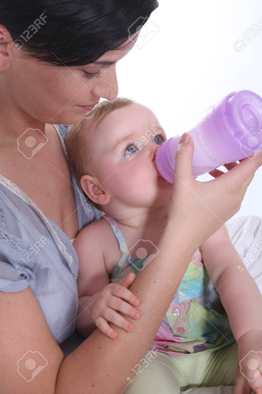 Girl giving baby her bottle Stock Photo - 12302509