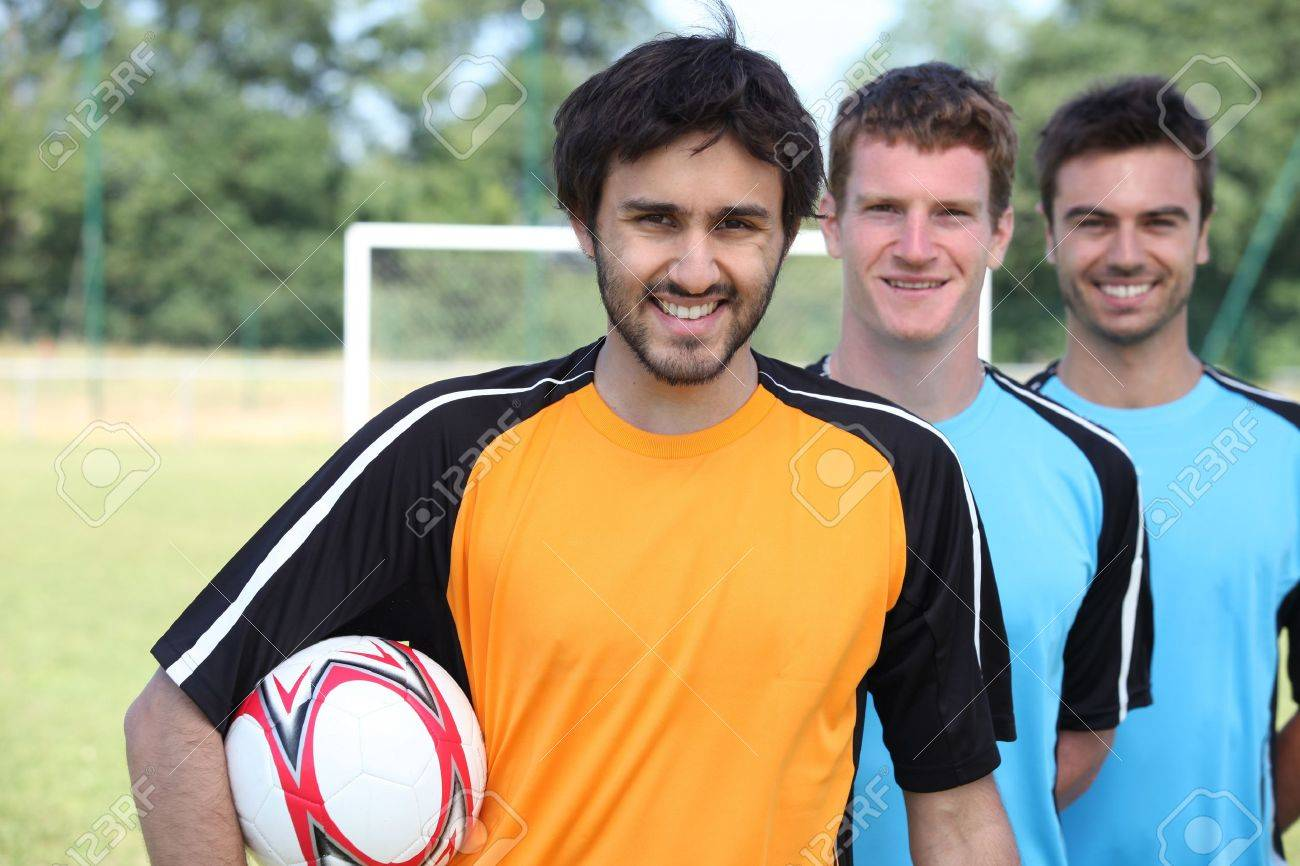Three footballers in a line-up in front of goal Stock Photo - 12302444