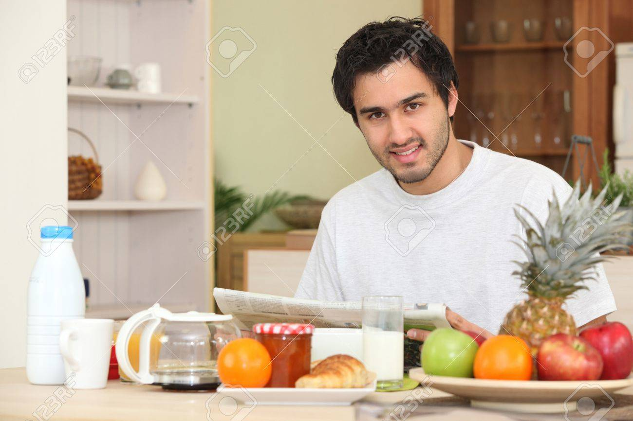 Man reading the newspaper while having breakfast Stock Photo - 12638187