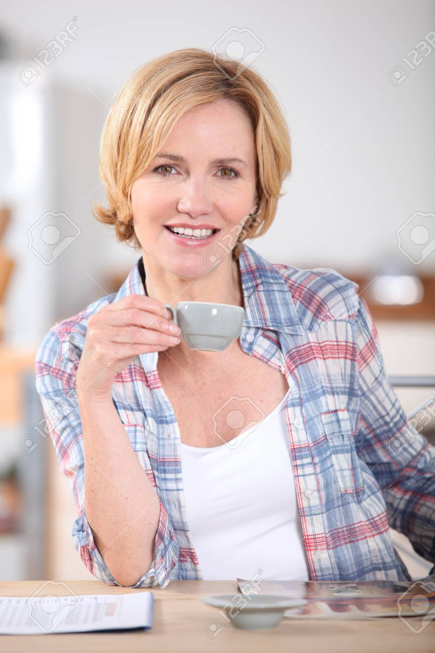 Woman having cup of coffee at kitchen table Stock Photo - 12595862
