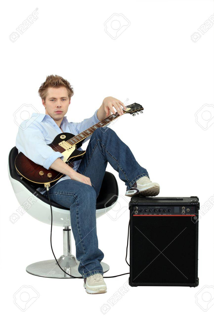 Boy in armchair with guitar and amp Stock Photo - 12905823