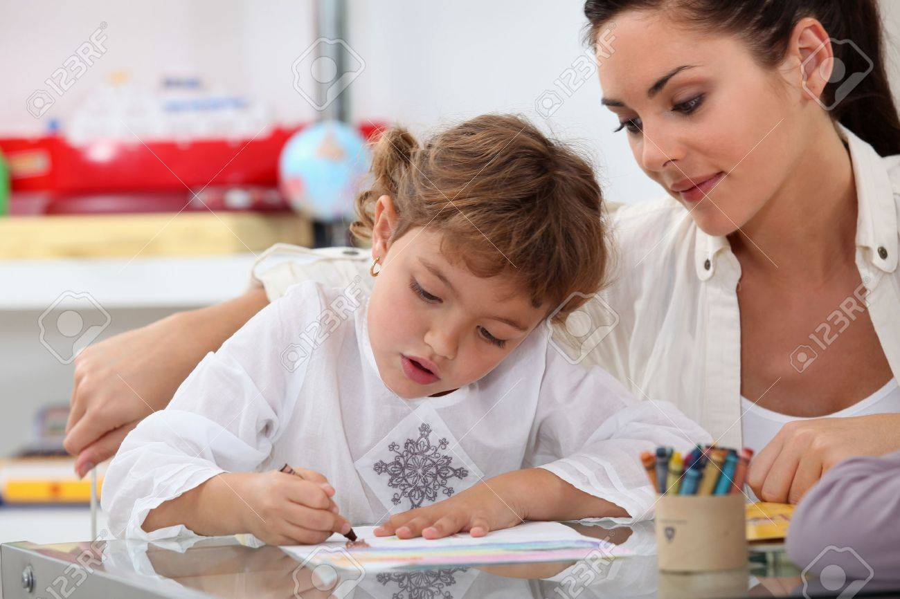 Teacher watching her pupil colouring a drawing Stock Photo - 12914960