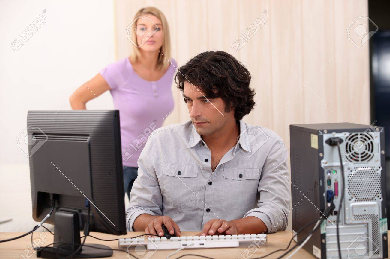 Male on his computer with his wife in the back Stock Photo - 12499630