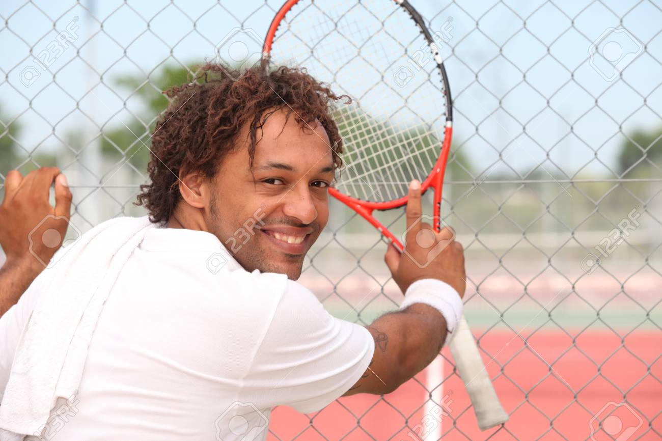 Male tennis player leaning on the fence of a municipal hard court Stock Photo - 12499956