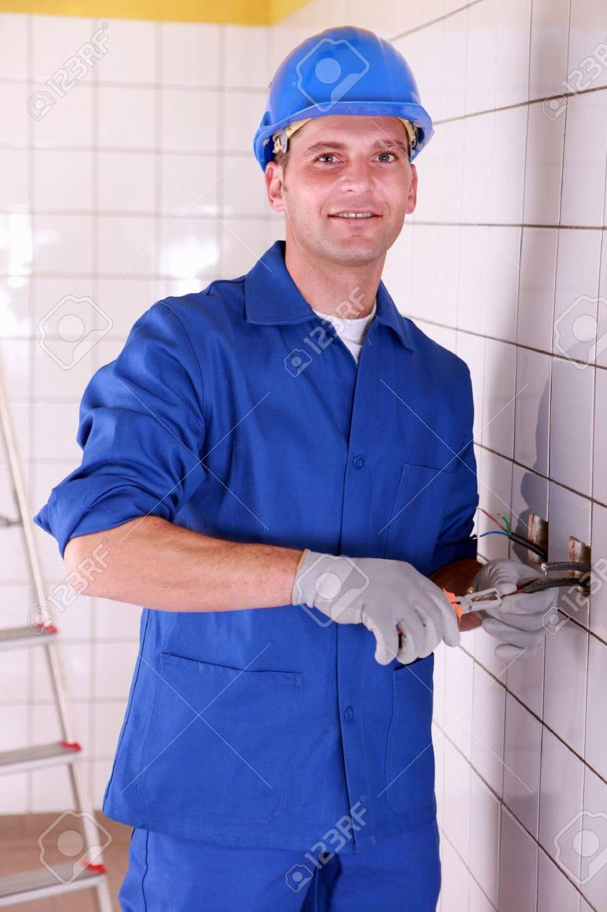 Tradesman installing electrical wiring Stock Photo - 12529579