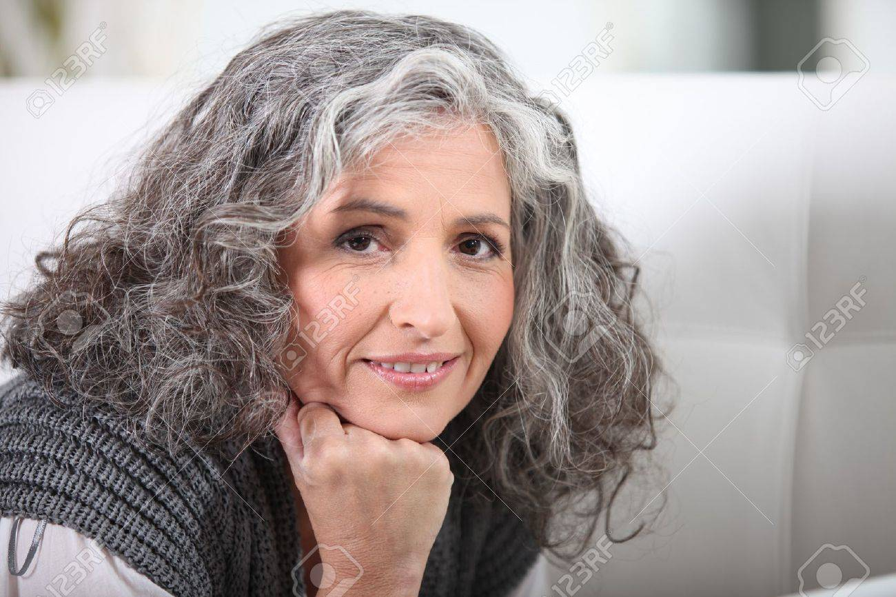 Grey-haired woman resting chin on hand Stock Photo - 13344080
