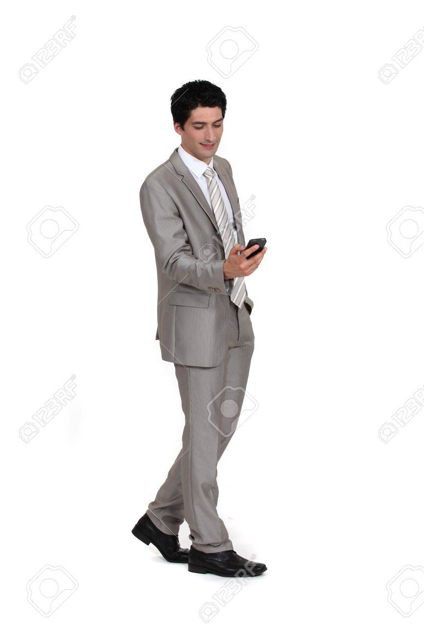 Young businessman sending text message whilst walking Stock Photo - 13377299