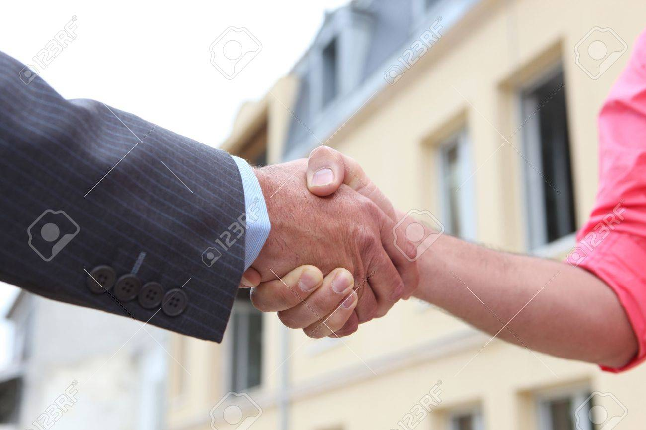 Couple shaking hands outside a house Stock Photo - 13560728