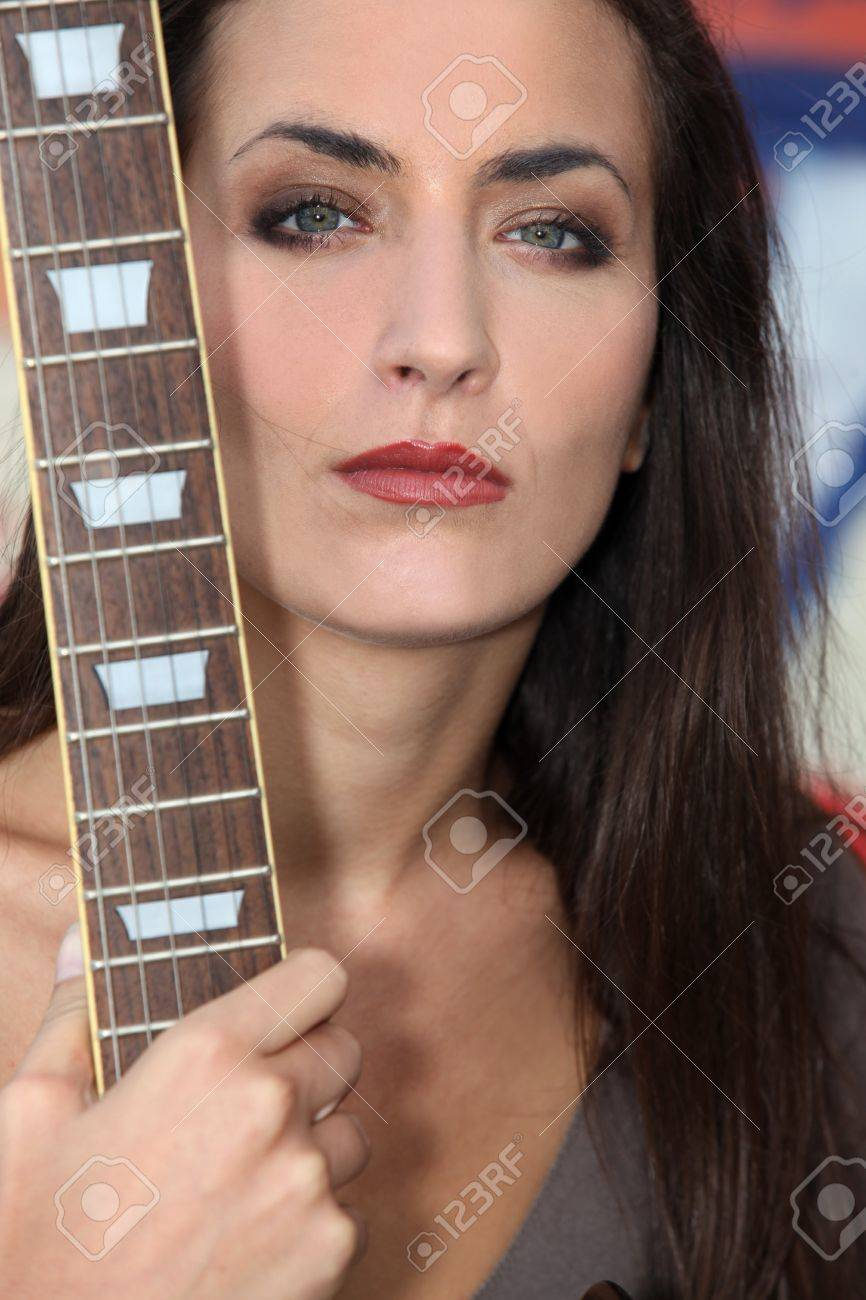 Unfriendly woman posing with her guitar Stock Photo - 13560450