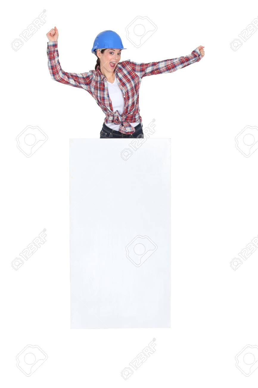 Enthusiastic construction worker with a board left blank for your message Stock Photo - 13561336