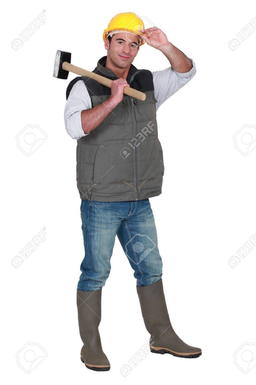 Tradesman carrying a mallet and wearing a hard hat and rubber boots Stock Photo - 13561187