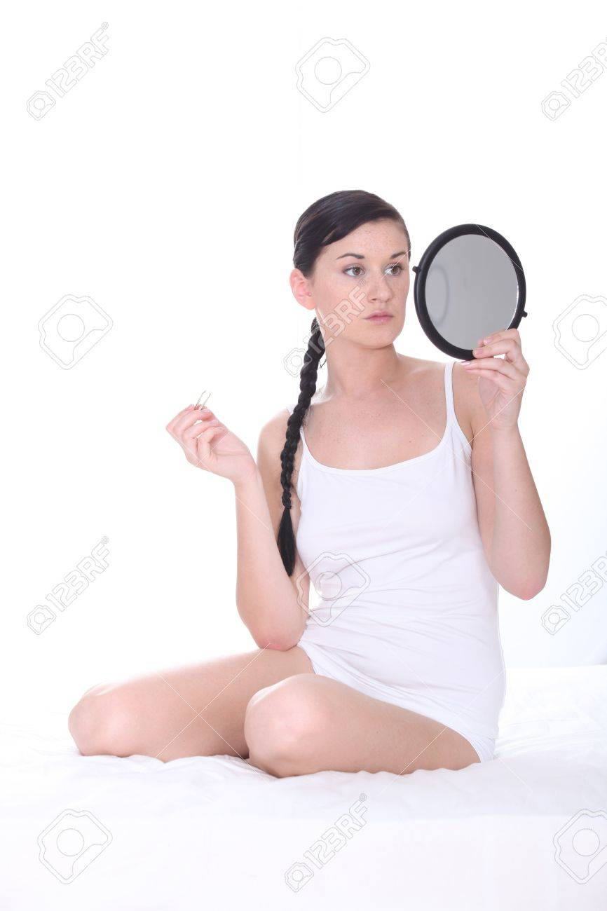 woman holding hand mirror. young woman sat on bed holding mirror stock photo - 13583988 hand