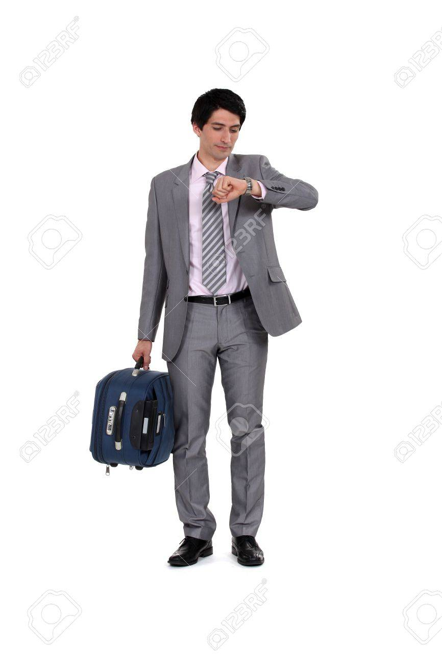 Man with suitcase looking at the time Stock Photo - 13584137