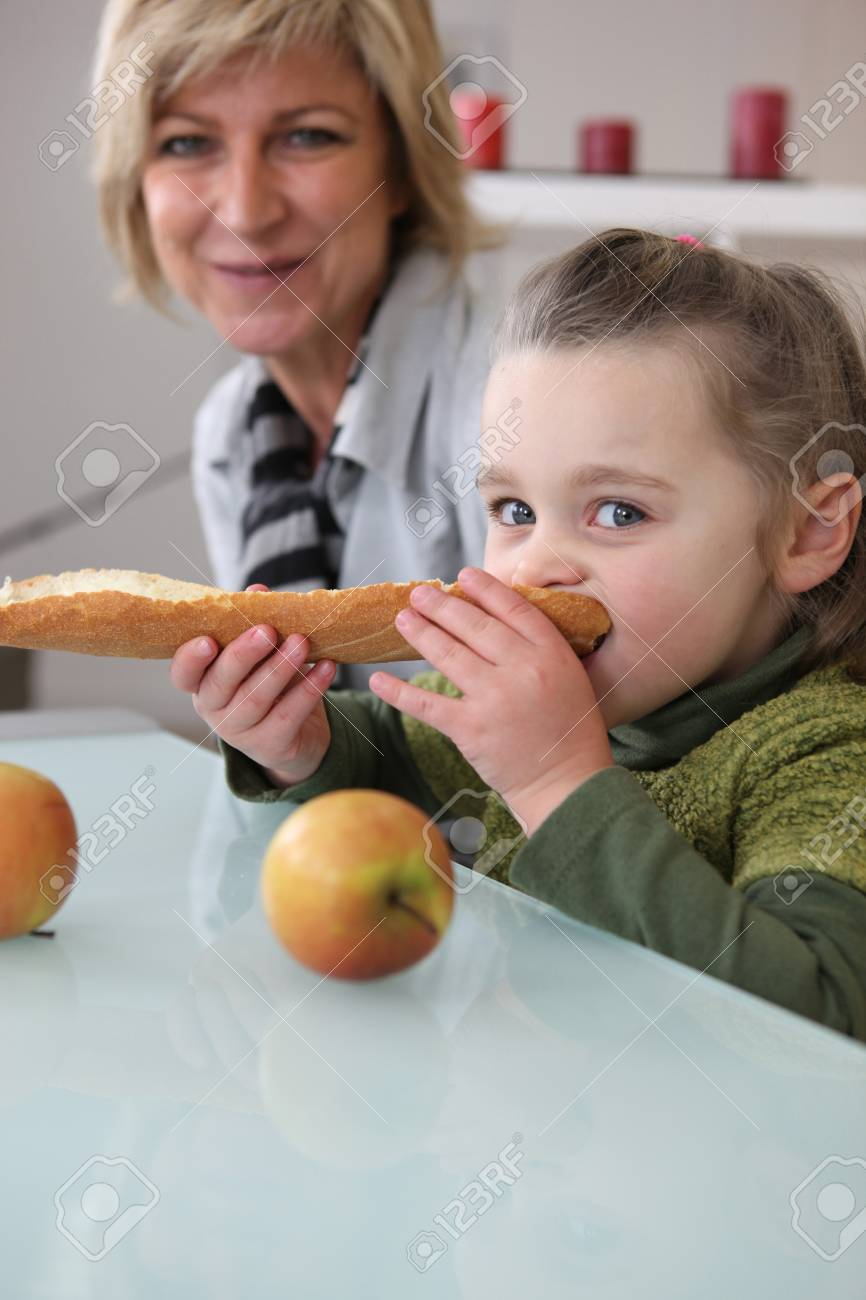 Little girl eating bread Stock Photo - 13582217