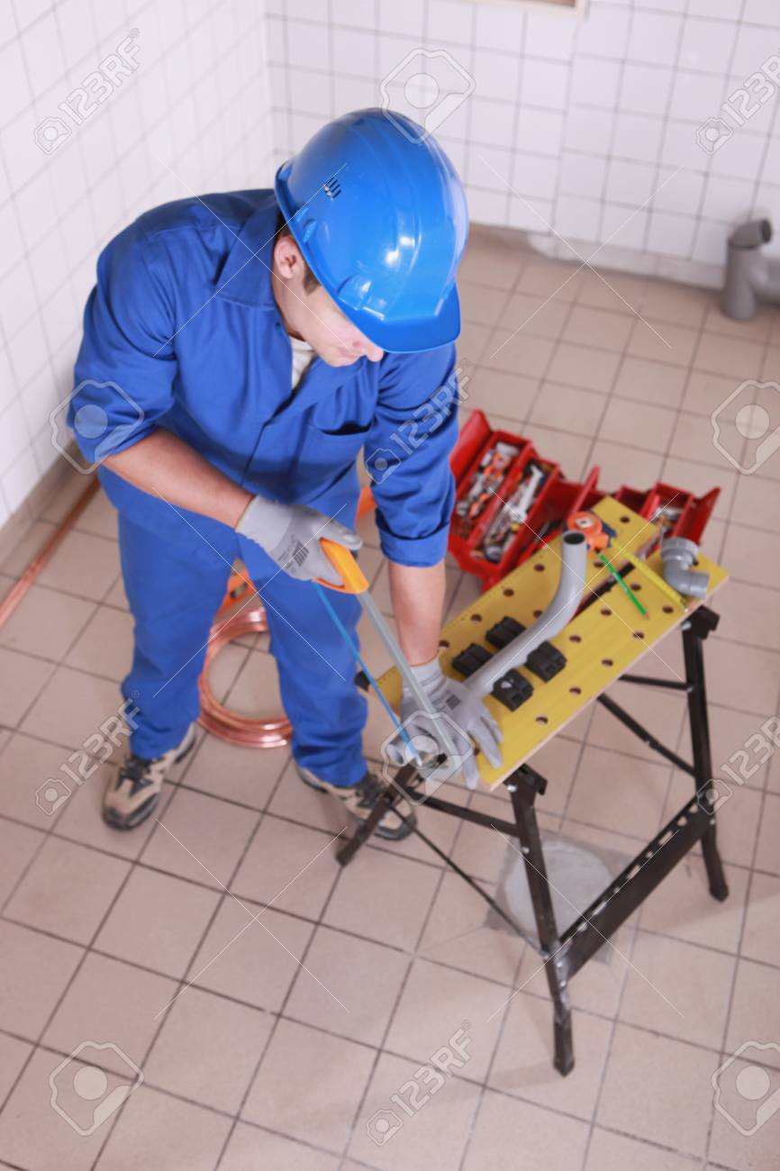 Plumber sawing plastic pipe Stock Photo - 13783388