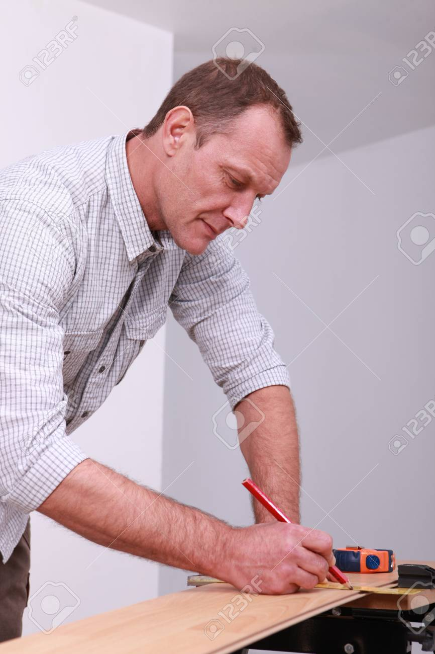 Man marking a floorboard with a pencil Stock Photo - 13812069