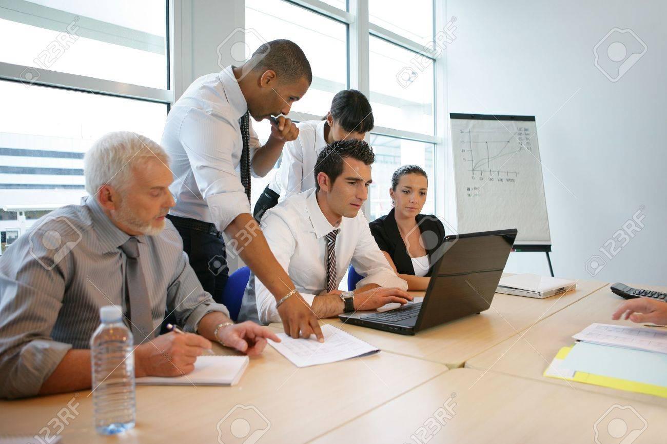 Office team working round a laptop computer - 13852318