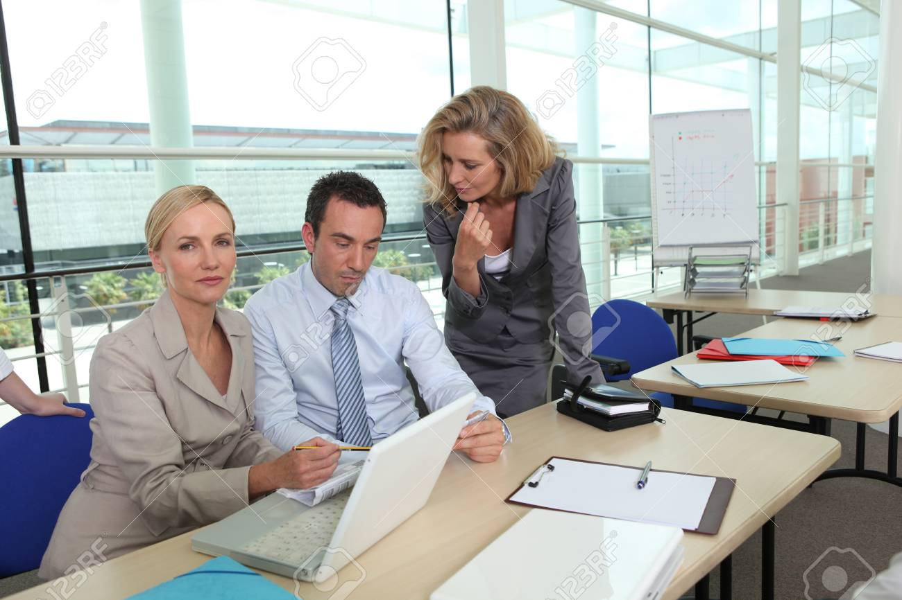 two women wearing suits and a man are working in a company Stock Photo - 13879126
