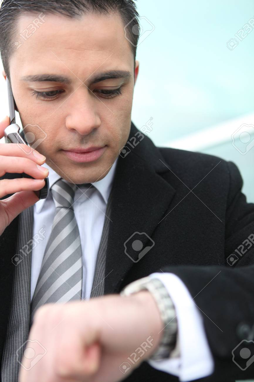Businessman checking he isn't late Stock Photo - 13845946