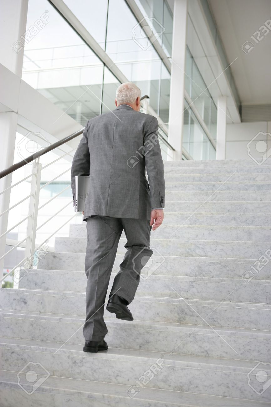 grey haired businessman climbing steps stock photo picture and