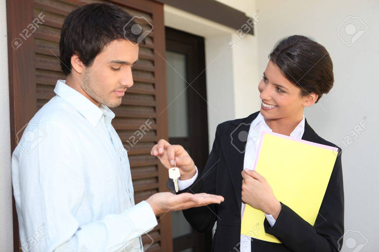 Estate agent handing over the keys to a new home Stock Photo - 13828304