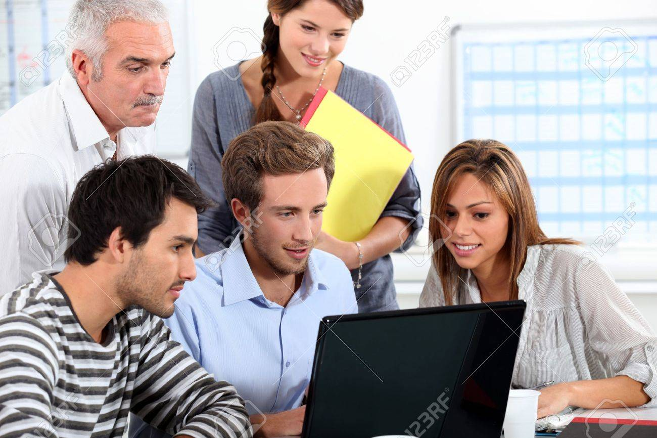 Informal team of people sitting round a laptop computer Stock Photo - 13839804