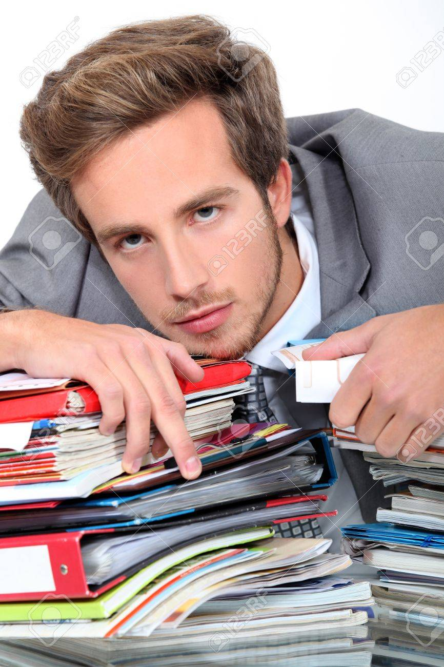 young man lying down on a desk full of binders and notebooks Stock Photo - 13867739