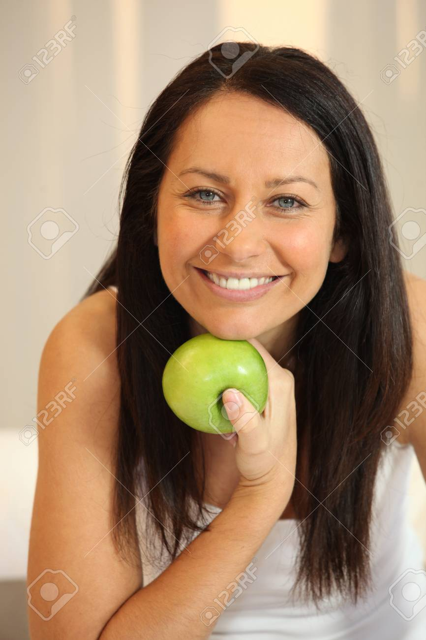 Portrait of a smiling woman with a Granny Smith apple Stock Photo - 13881911