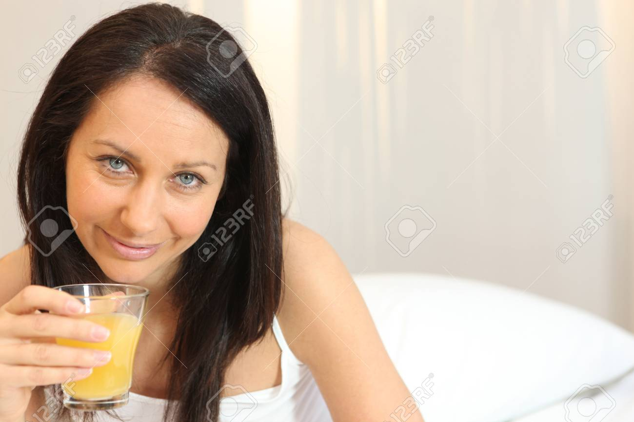 Woman at home with glass of orange juice Stock Photo - 13881435
