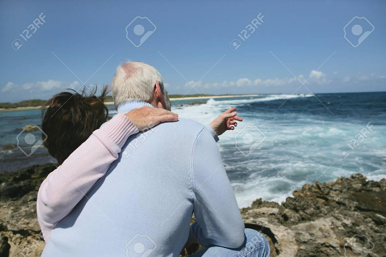 Senior couple pointing towards the sea Stock Photo - 13915711