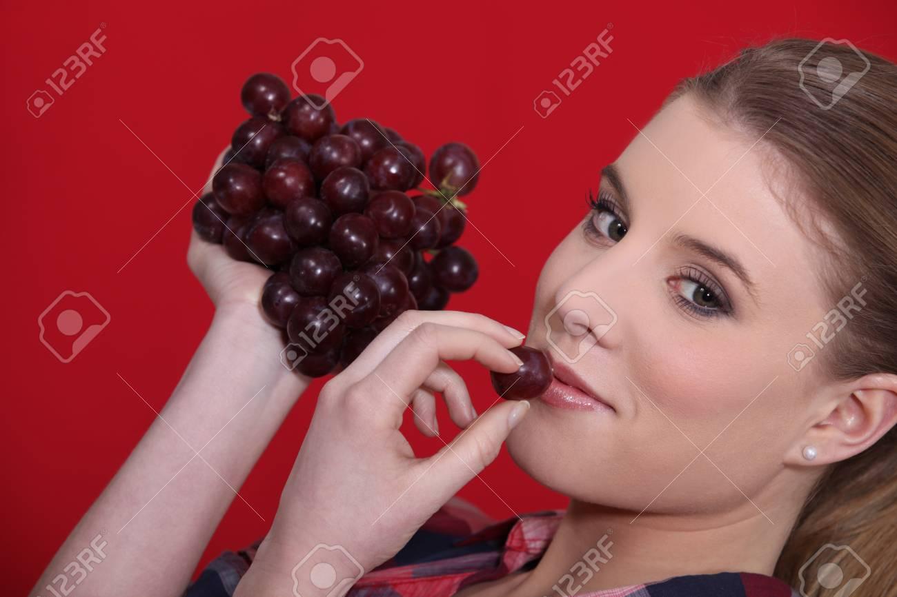 Woman eating grapes Stock Photo - 13960297