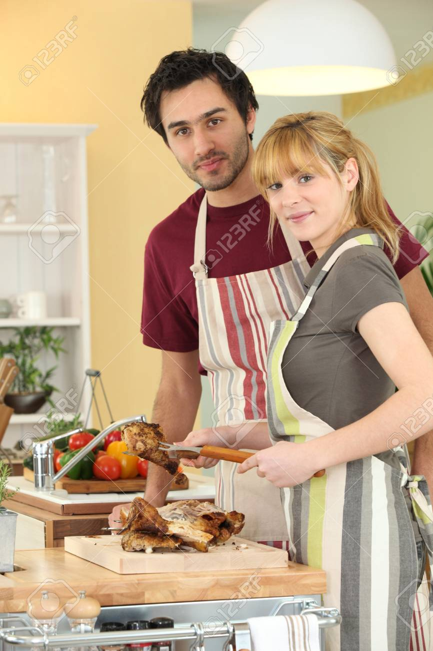 Young man and young woman cutting chicken Stock Photo - 13988880