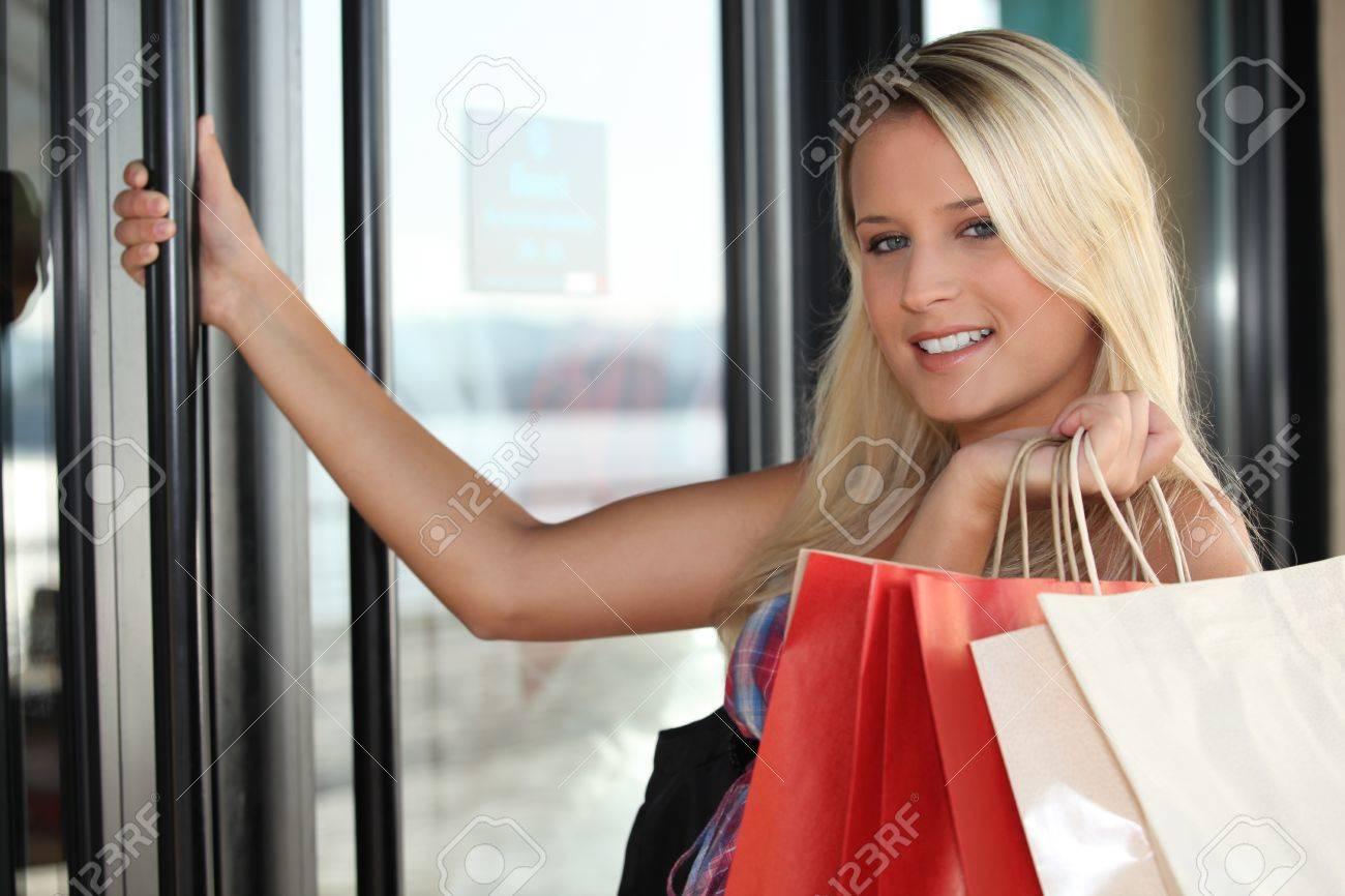 Blond woman opening shop door Stock Photo - 13957965