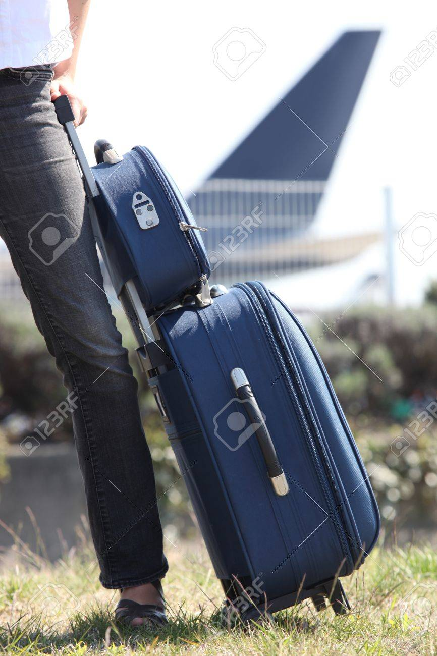 Woman with a suitcase at an airport Stock Photo - 13976802