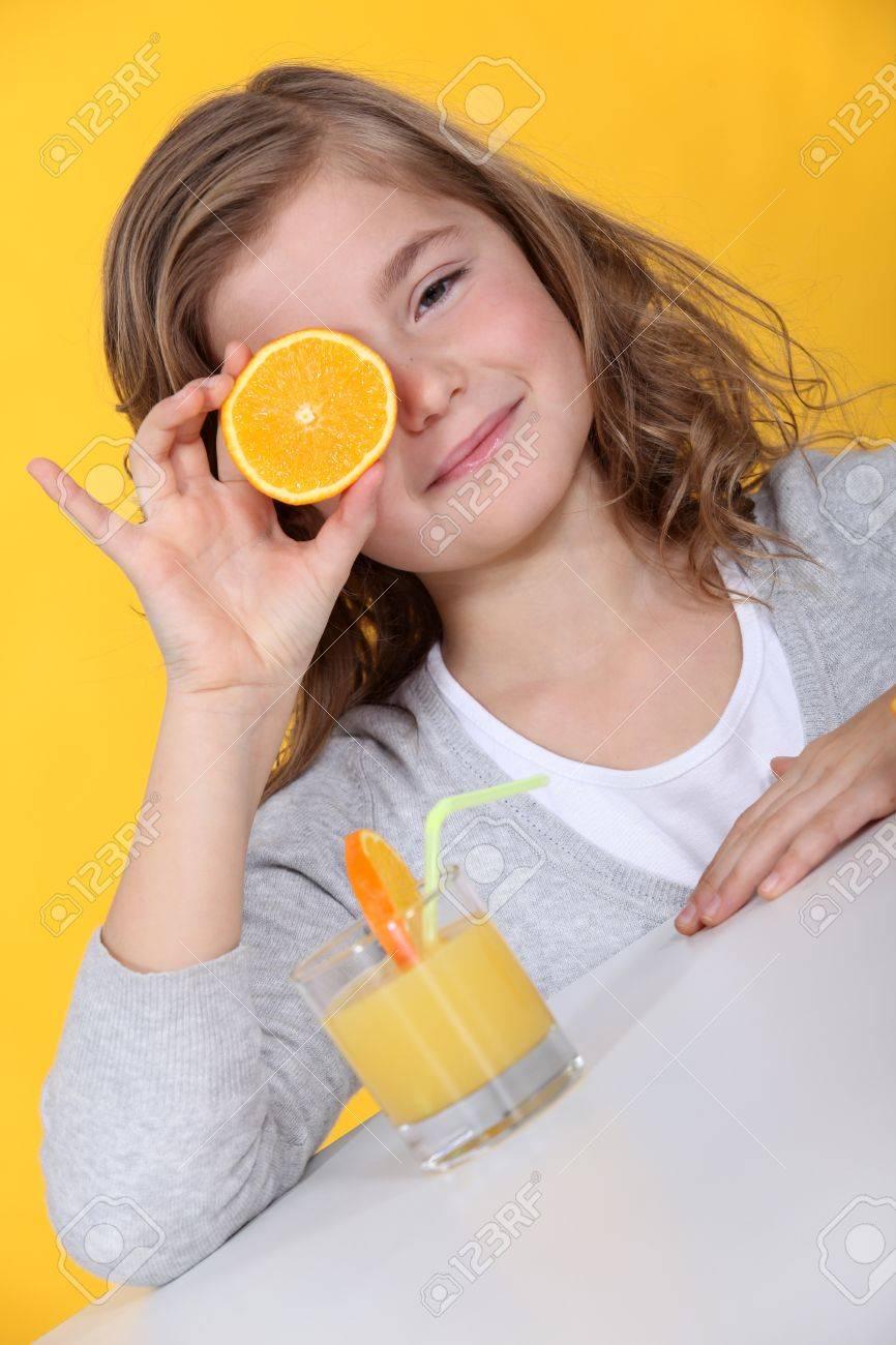 Girl covering her eye with orange slice Stock Photo - 14105784