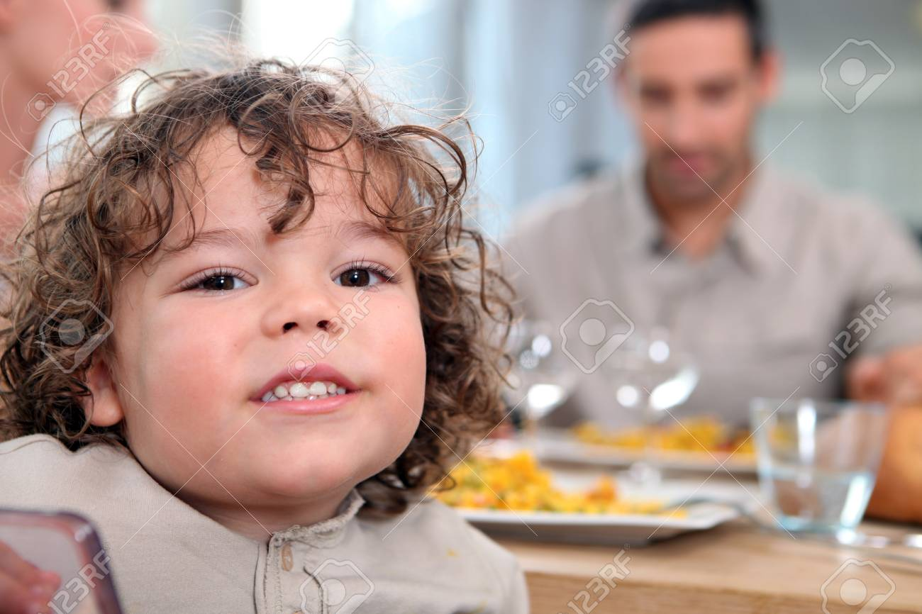 Young girl having a meal with her family Stock Photo - 14111396