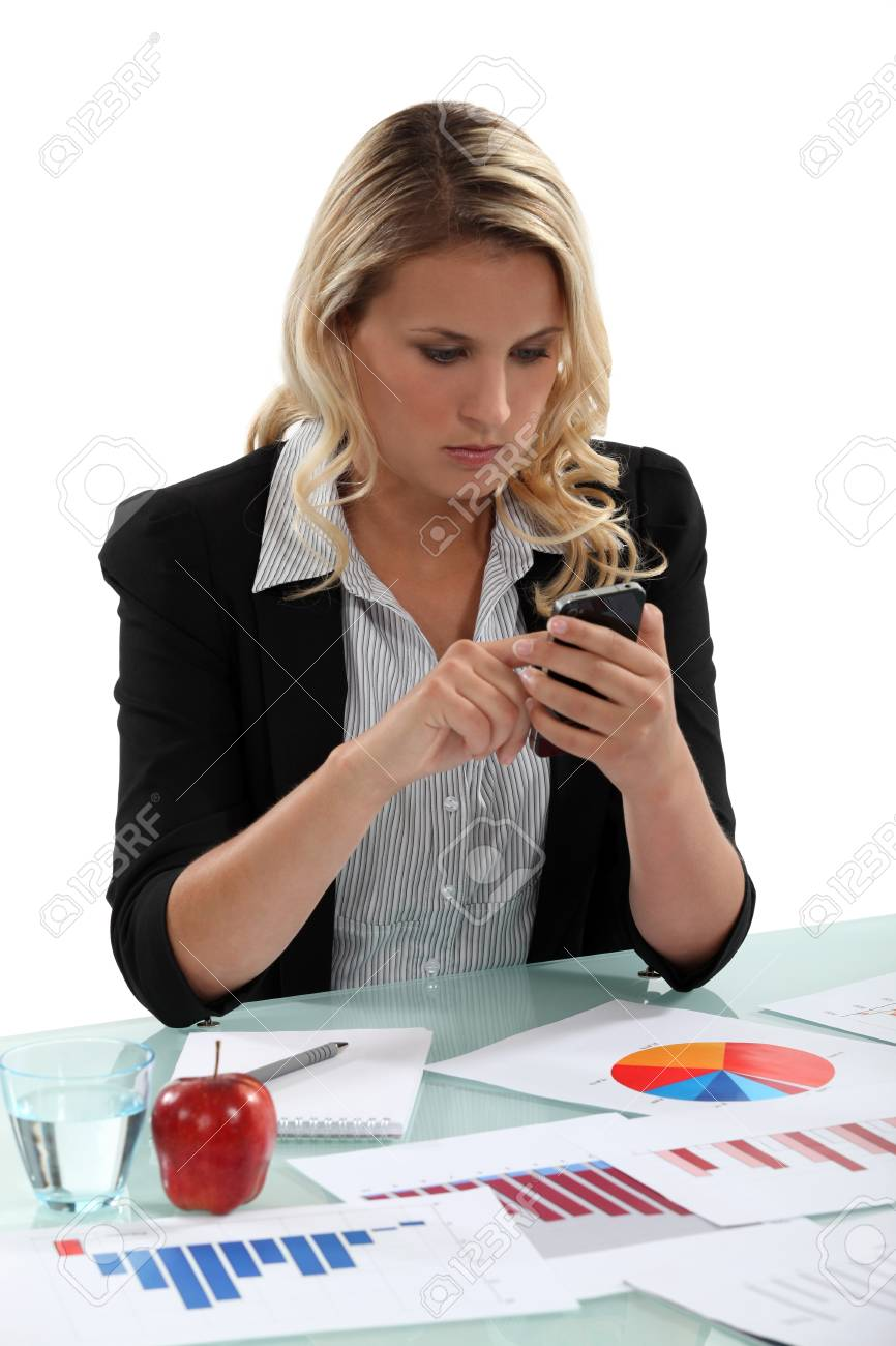 A businesswoman texting with charts on her desk. Stock Photo - 14195354